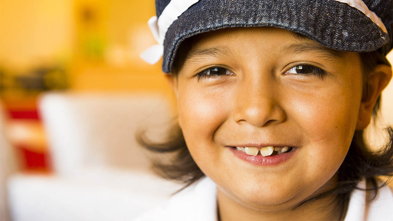A close up of a smiling girl wearing a hat