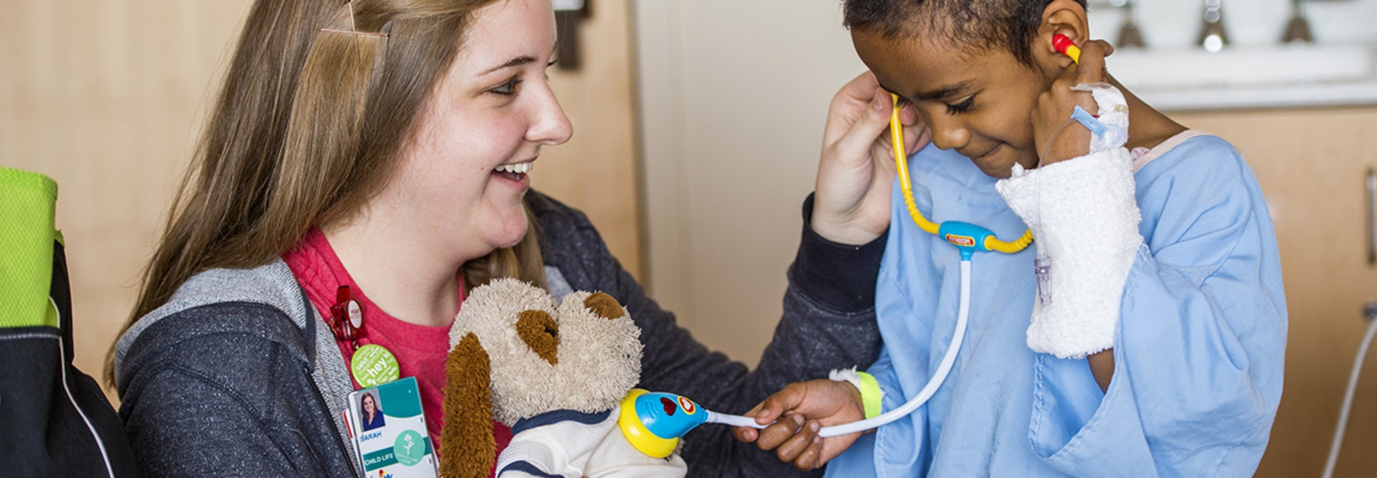 A child life specialists helps a kid listen to a stuffed animal's heartbeat with a toy stethoscope.