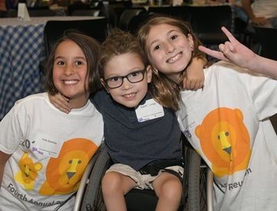 Three kids are wearing name tags and smiling. A boy with glasses, a grey shirt and a wheelchair is between two