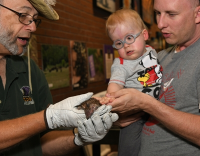 A zookeeper in a green shirt holds a small animal in his gloved hands. A man holding a blonde baby wearing glasses touches the animal.