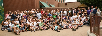 A group of about 100 people pose for group photo at the Denver Zoo.