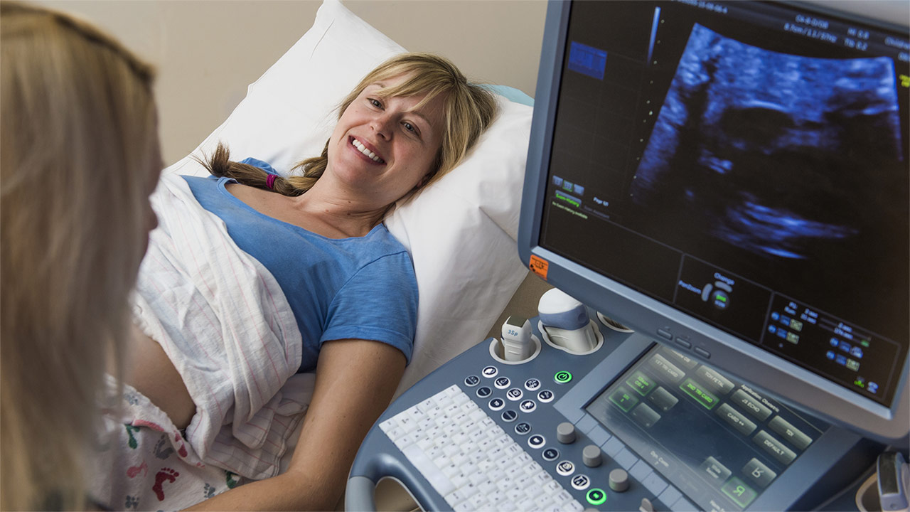 A woman performs an ultrasound on a fetal cardiology patient.