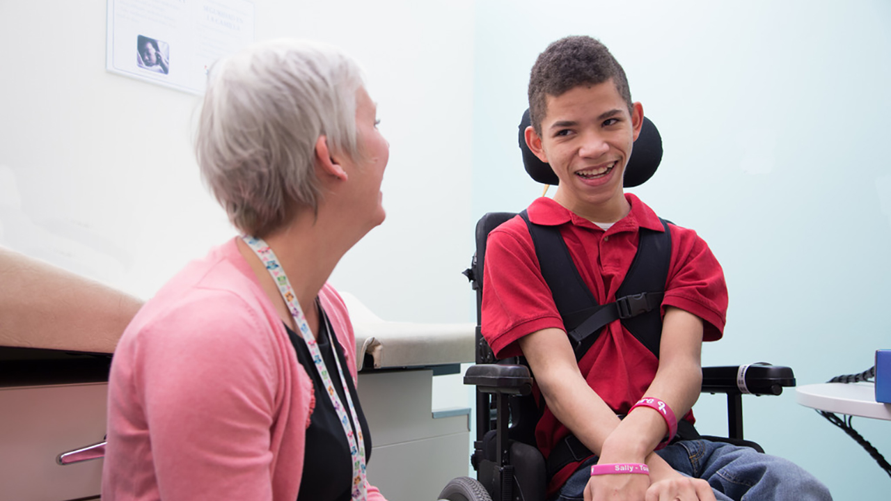 A boy wearing a red shirt sits in a wheelchair laughing with his doctor who is wearing a pink cardigan.