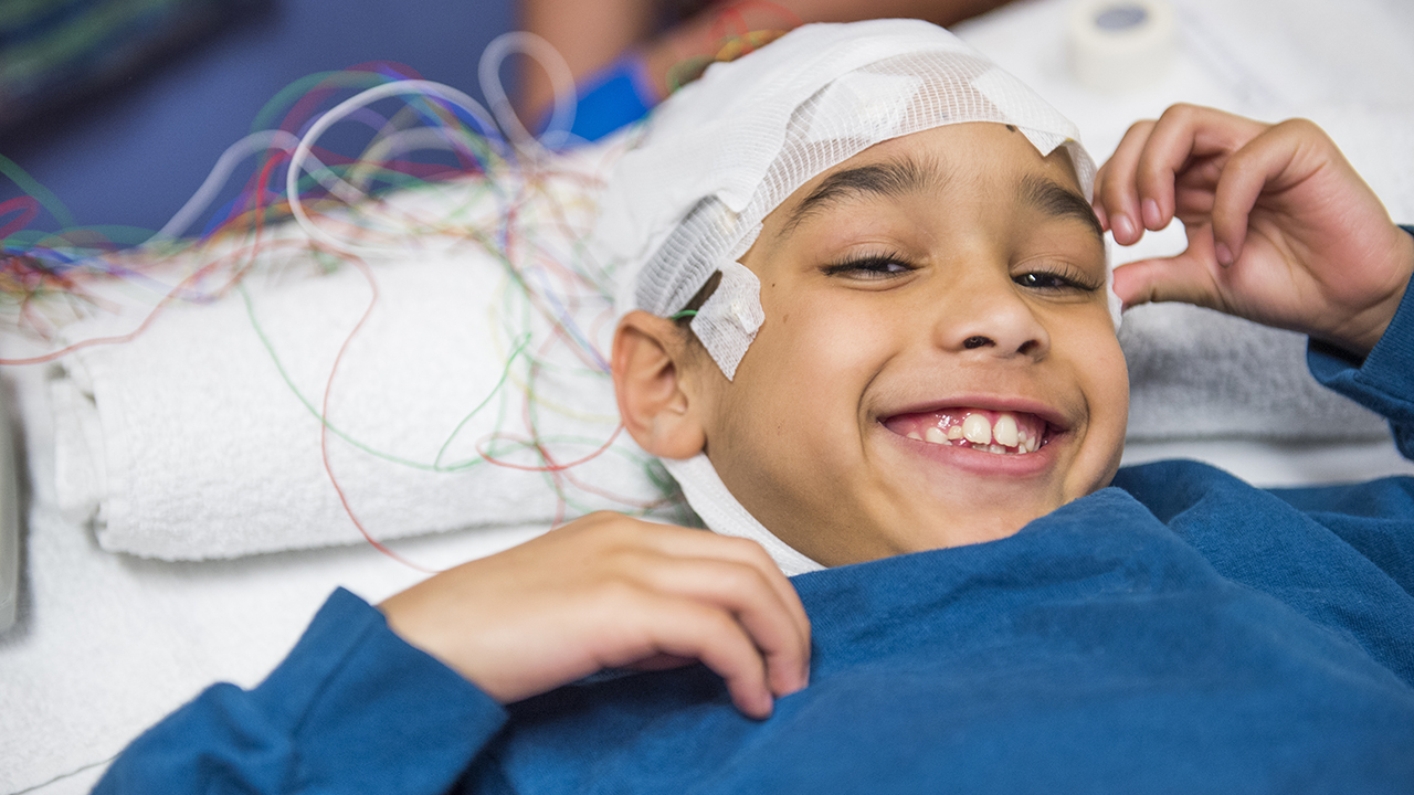 A boy in a blue shirt lies in a bead with his head wrapped in bandages and hooked up to sensors
