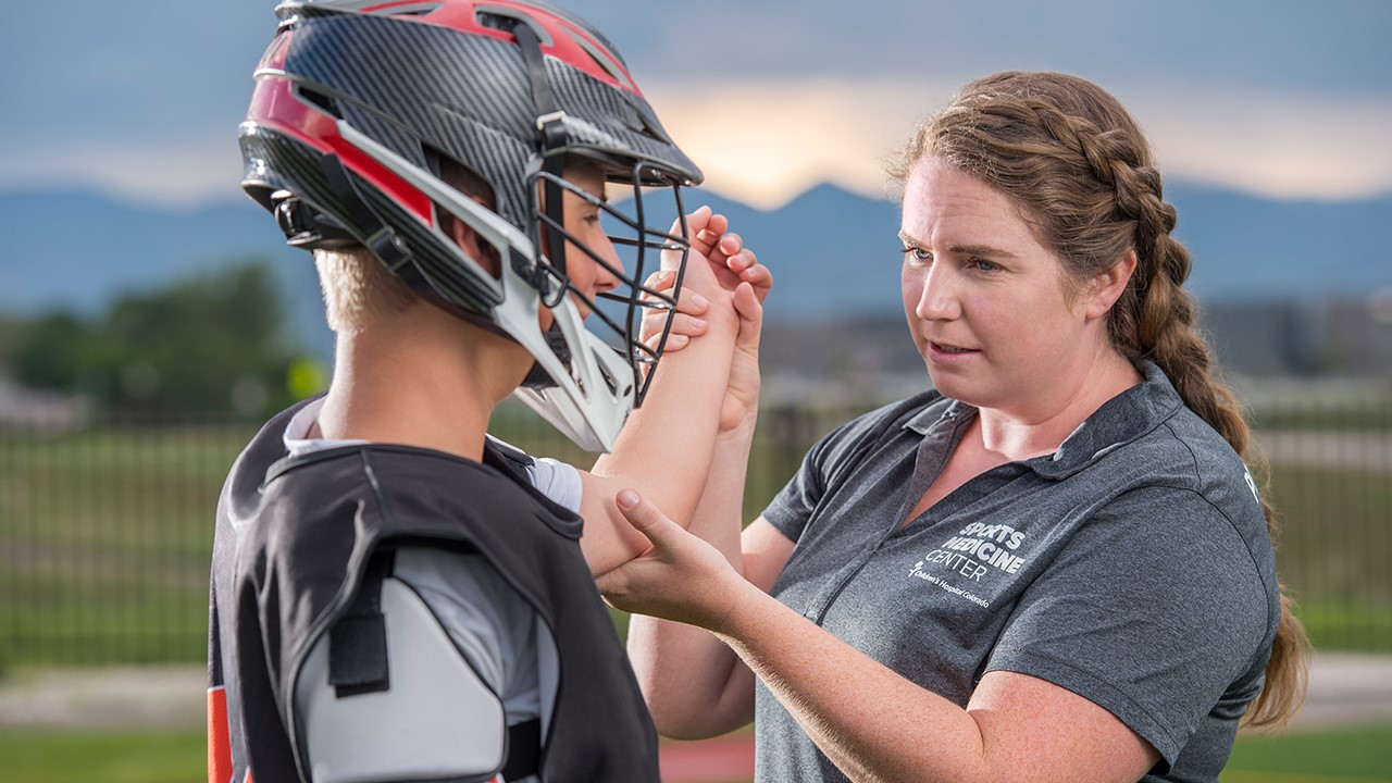 Athletic trainer checks lacrosse player's elbow.