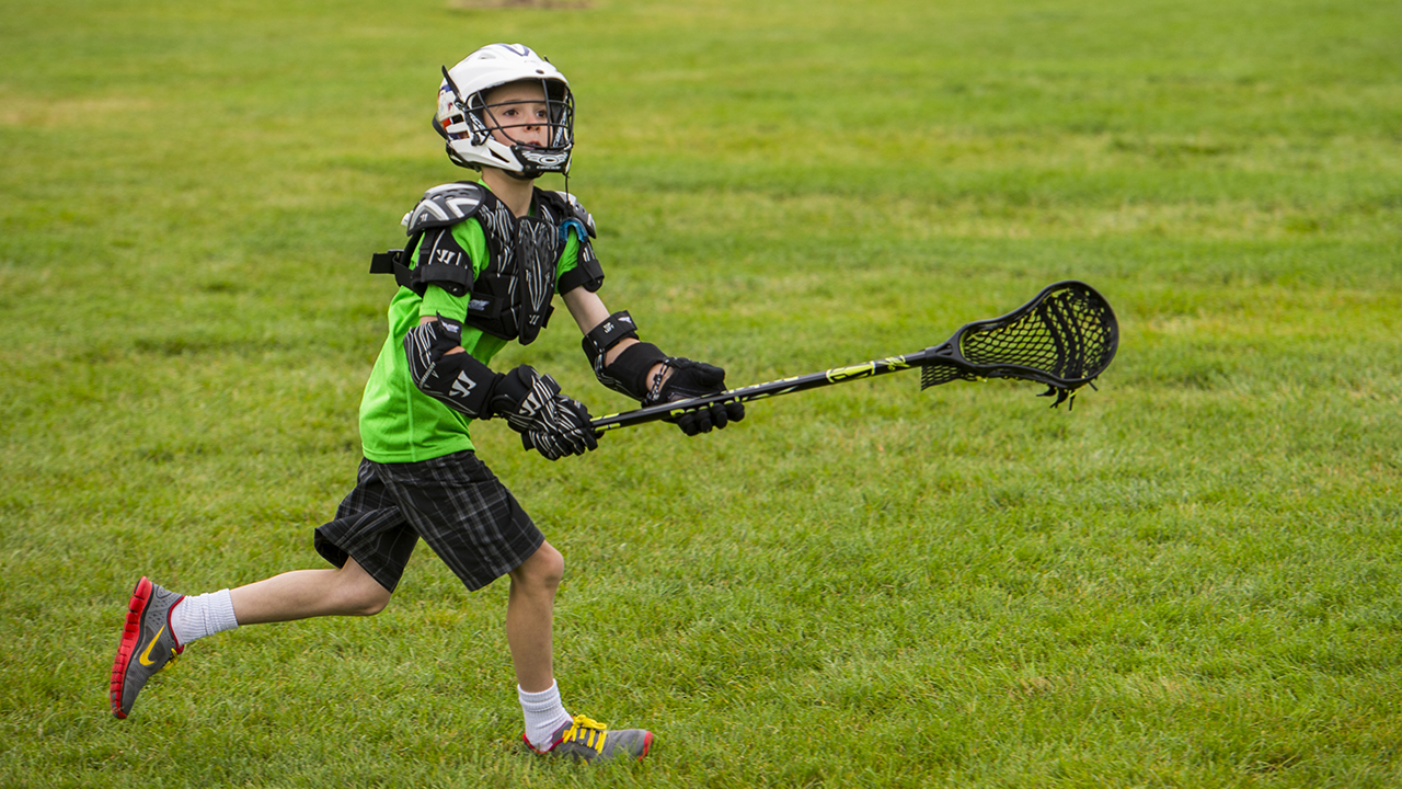 A boy wearing a green shirt, white helmet, black shoulder pads and black gloves runs while holding a lacrosse stick with a ball in it.