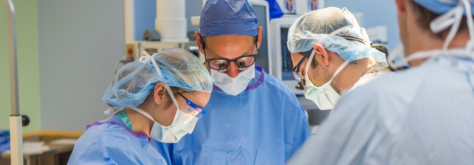 Dr. Duncan Wilcox, Surgeon-in-Chief, performing surgery with other healthcare providers in the operating room