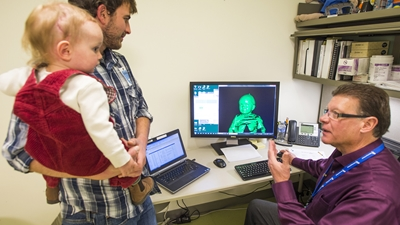 A dad in a plaid shirt holds a baby in red corduroy overalls while he points to a 3-D image on the computer screen.