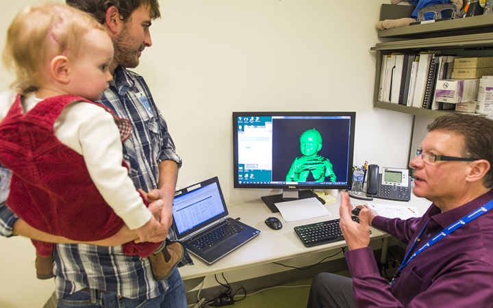 A dad in a plaid shirt holds a baby in red corduroy overalls while a physician discusses the 3-D image on the computer screen.