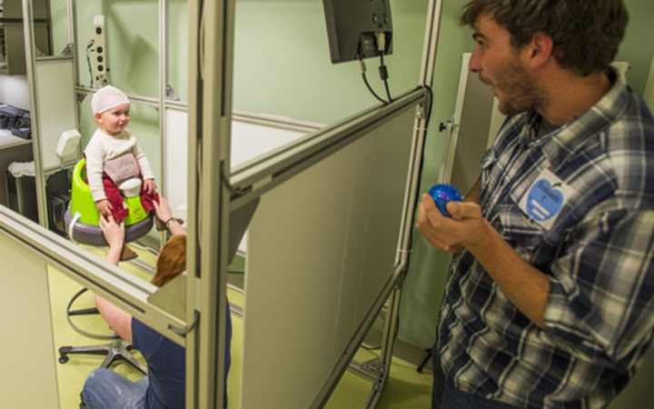 A mother holds a baby still while the dad in a plaid shirt holds a bright blue ball to entertain the baby during imaging.