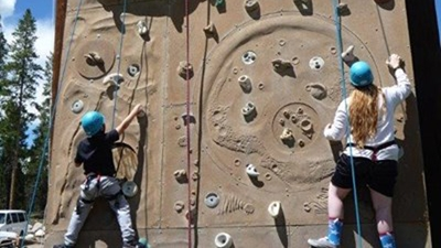 A boy wearing a black shirt, jeans and light blue helmet climbs up the left side of a climbing wall while a girl with long hair and wearing a white shirt, black shorts and light blue helmet climbs up the right side.