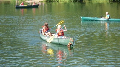 Two girls wearing orange life vests paddle a green canoe on a river while a counselor watches from a green kayak and two kids in the background paddle a black canoe.