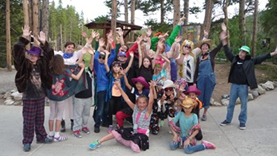 A group of kids with their hands up cheering pose on a cement trail in a wooded area. They are wearing a variety of clothes including wigs, cowboy hats, feather boas, ski goggles, ties and bandanas.