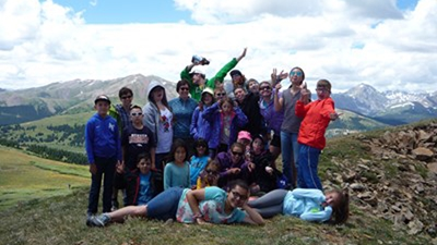 A group of kids, some in t-shirts and some wearing jackets, gather at the top of a mountain to celebrate their hike to the top. Most are doing fun poses and the tallest in the back is dabbing.