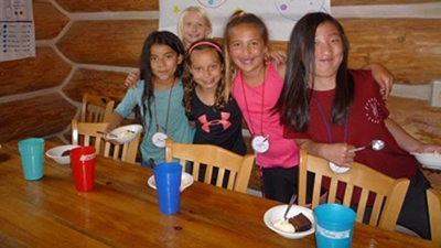 A group of five girls wearing bright summer clothes stand behind a wood table with bright colored cups and white plastic bowls filled with brownies and vanilla ice cream.