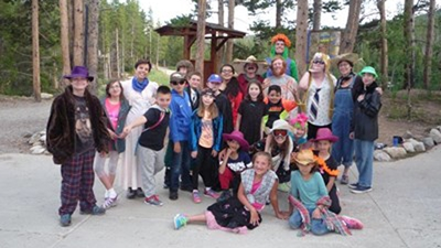A group of kids pose on a cement trail in a wooded area. They are wearing a variety of clothes including wigs, cowboy hats, feather boas, ski goggles, ties and bandanas.