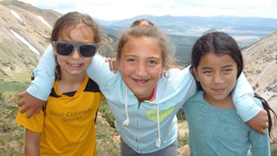Three girls pose at the top of a mountain. The girl on the left is wearing a gold and black Real Colorado shirt and sunglasses. The girl in the middle is wearing a light blue hooded zipup sweatshirt. The girl on the right is wearing a blue-green long sleeve shirt.