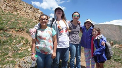 A group of five girls wearing brightly colored clothes stand near the top of a mountain on a hiking trail.