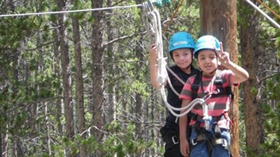 A boy wearing a red and gray striped shirt, jeans and light blue helmet makes the peace sign while standing on a platform in a forest and hooked up to a zipline. There is a boy standing behind him all black and a light blue helmet.