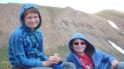 Two boys in hooded blue sweatshirts and jeans sit on an open mountain side with a blue water bottle and ziploc baggie full of snack food.