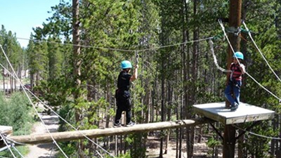 A boy wearing a red and gray striped shirt, jeans and light blue helmet stands on a platform watching a second kid wearing all black and a light blue helmet walk across a log while connected to a zipline in a forest.