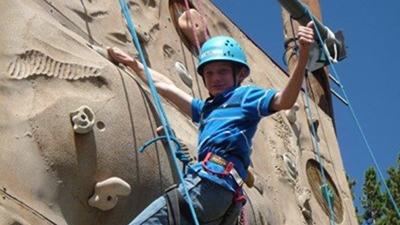 A boy wearing a blue striped polo, jeans and light blue helmet stands at the top of a climbing wall and gives a thumbs up.
