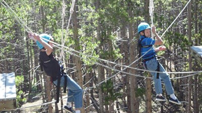 Two boys wearing light blue helmets, t-shirts and jeans swing along a zipline in the forest.