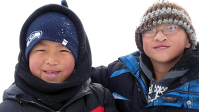 Two boys wearing ski jackets and winter hats stand in the snow with pine trees in the background.