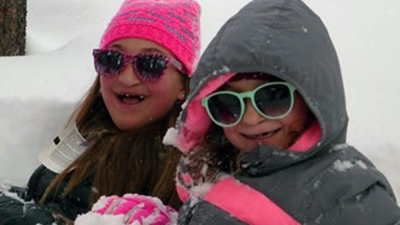 Two girls in sunglasses and ski jackets sit in the snow at Cleft Camp.