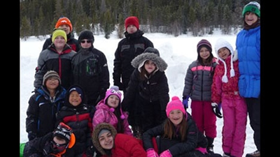 A group of 13 kids wearing ski jackets and pants pose for a group picture in the snow with pine trees in the background.