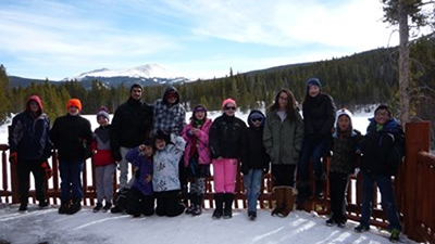 A group of kids in ski outfits line up along a fence on a snowy mountain side.