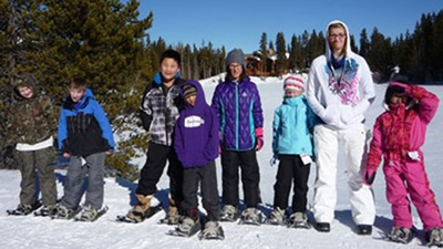 A group of 7 kids wearing ski jackets and pants stand together on a snowy mountain with pine trees around.