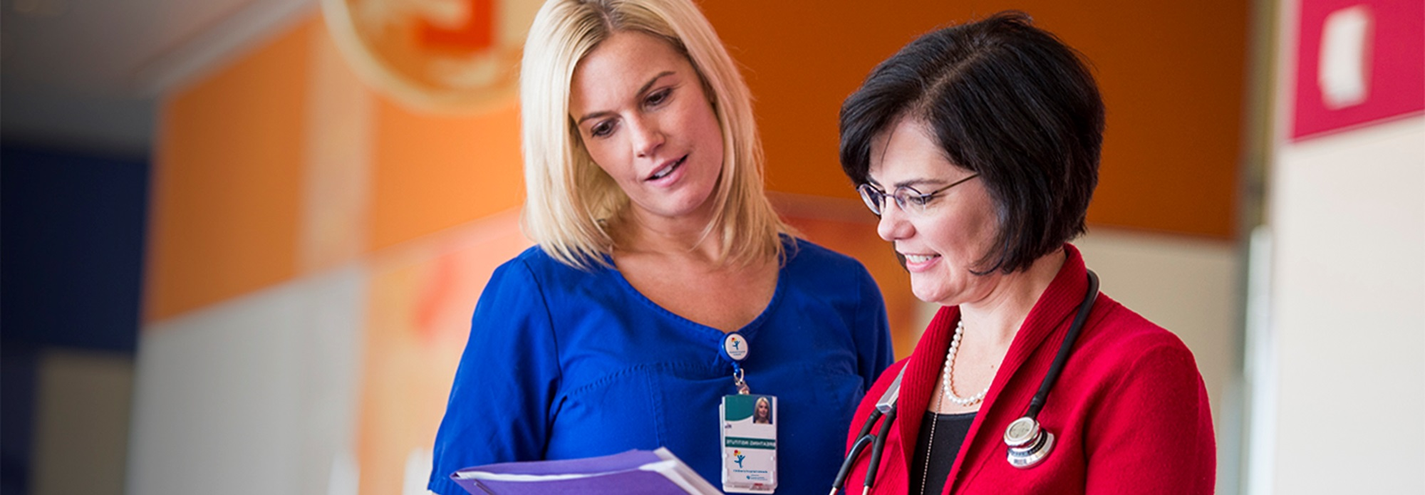 Two women healthcare professionals looking at a medical chart.
