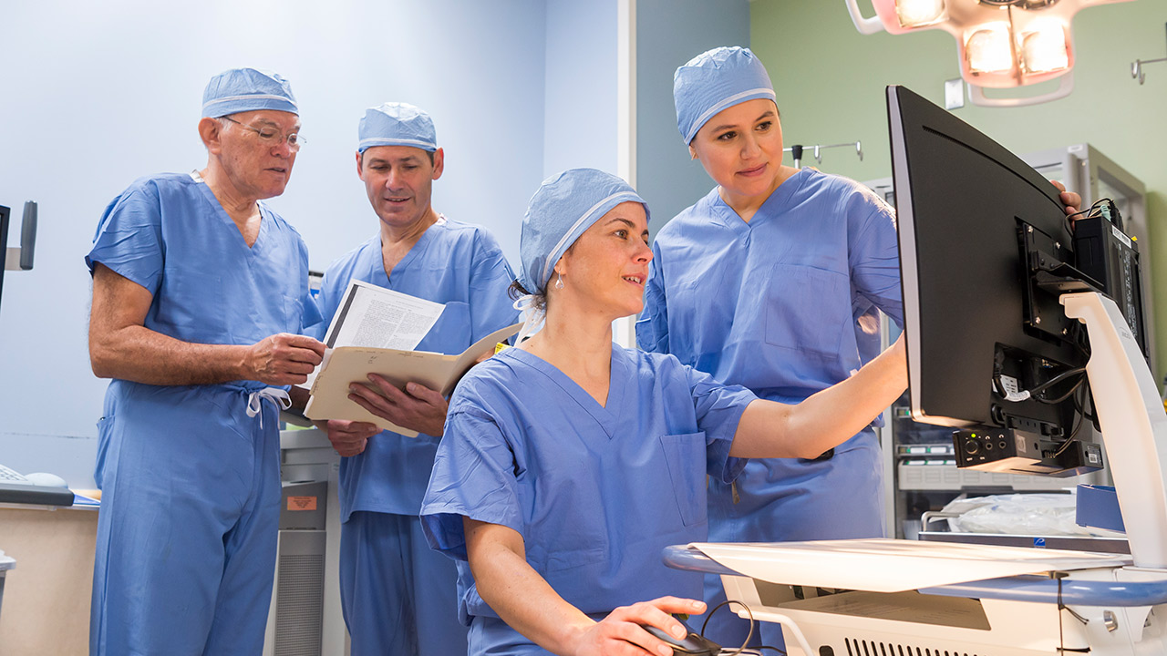 Four physicians in scrubs review a cloacal anomaly case.