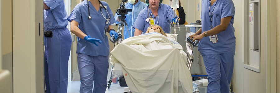 Healthcare professionals move a simulation doll on a gurney in a hospital hallway