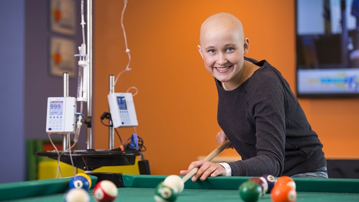 Patient playing pool in Children's Colorado's Teen Zone