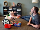A baby sits in a special seat made for her spina bifida while handing daddy a couple of shape blocks.