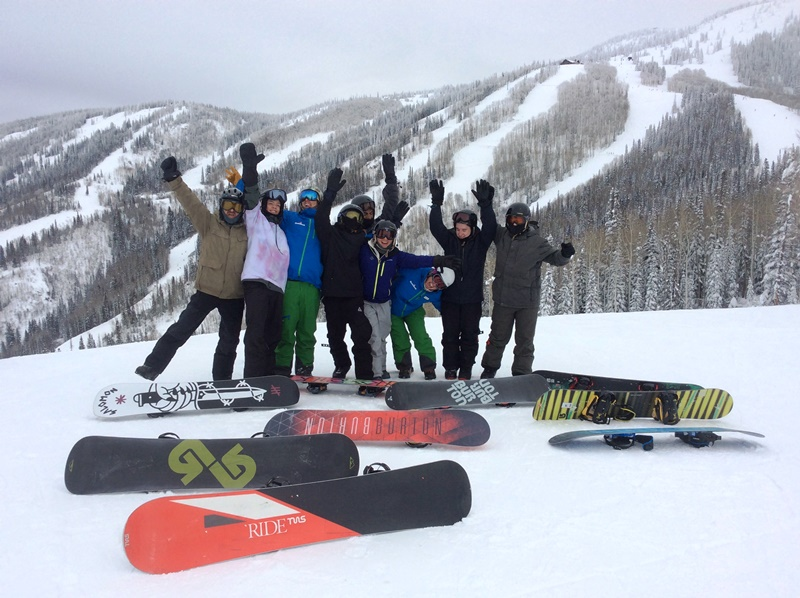 A group of kids in full ski gear, with snowboards, pose together on a mountain at Children's Hospital Colorado's winter burn camp.