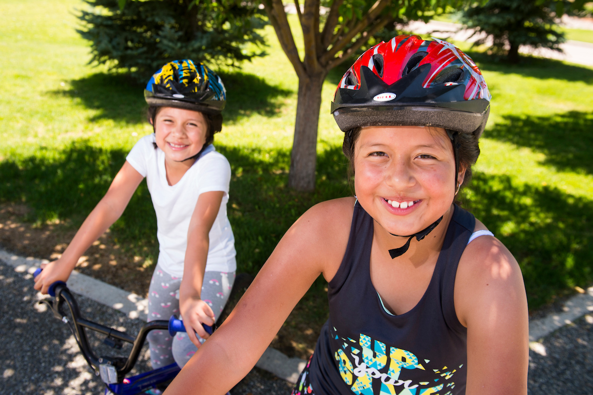 Two hispanic children smiling on their bikes in a park.