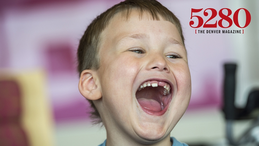 A young boy with short brown hair is smiling with his mouth open. He is missing one of his front teeth. There is a logo in the top right corner for 5280 magazine.