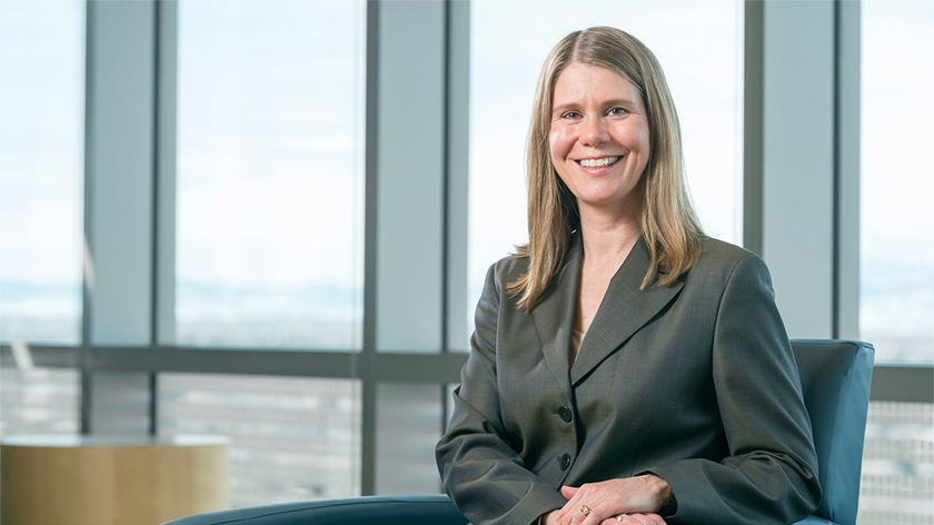 Photo of CEO, Jena Hausmann of Children's Hospital Colorado sitting in a chair wearing a suit jacket.