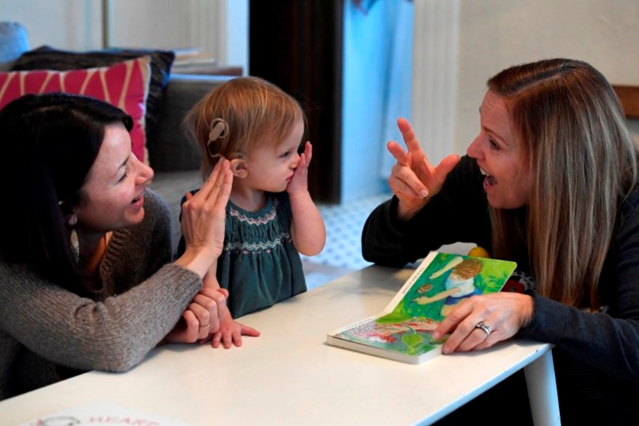 A provider and mom read a book with a child who has CMV, which is the most common nongenetic cause of childhood deafness in the country.