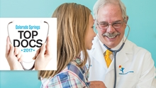 A male doctor with a mustache uses a stethoscope to check a young patient. The Colorado Springs Style Top Docs logo is overlaid on the image.