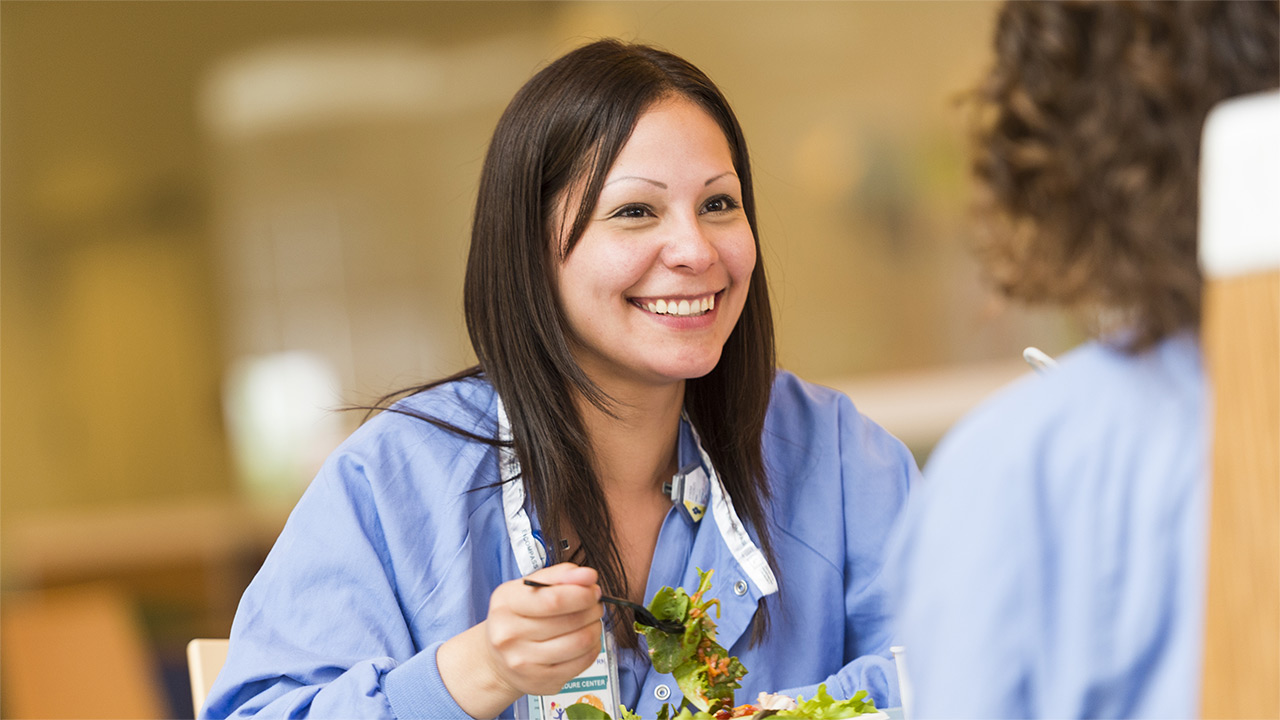 A smiling woman in medical scrubs is eating a salad.