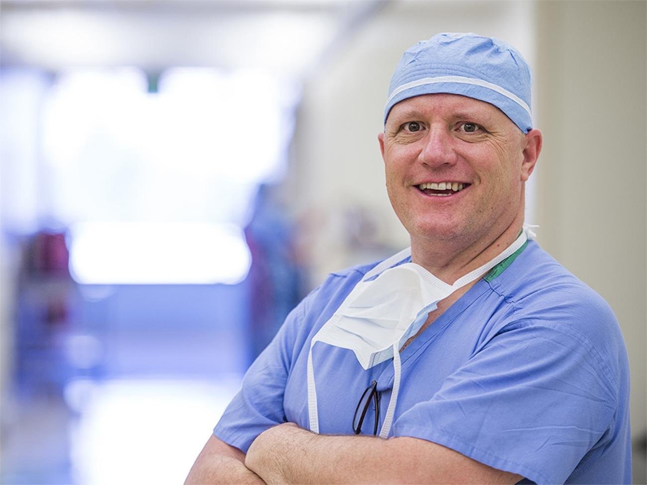 A male doctor wearing blue scrubs has his arms crossed and he's smiling at the camera.