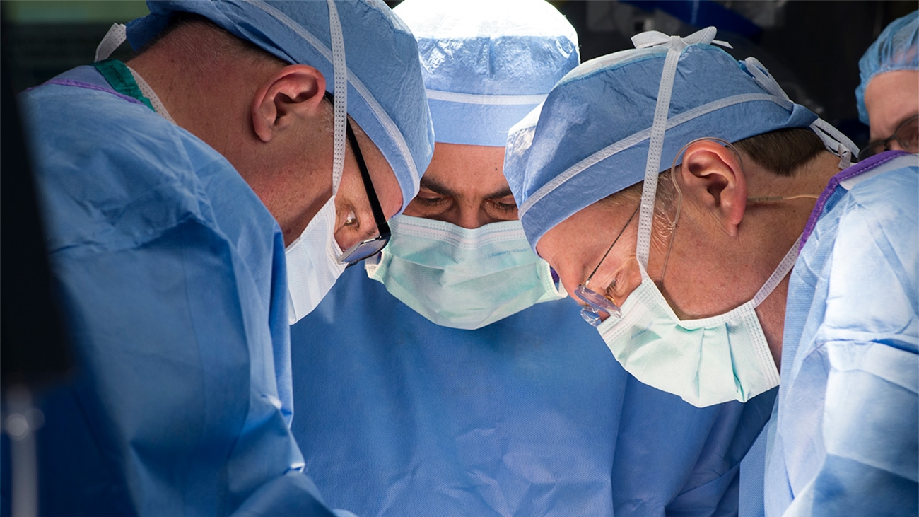 Three surgeons are dressed for a procedure with facemasks on. The surgeons are leaning over with their heads together during a procedure to treat spina bifida.