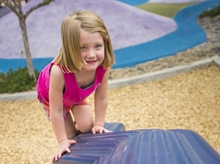 A girl with blonde hair and wearing a pink tank top plays at a playground.