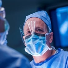 Dr. Henry Galan wearing protective eyewear and a face mask during surgery.
