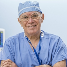 Dr. Alberto Pena smiles at the camera wearing blue scrubs and a surgical cap.