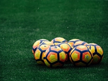 Brightly colored soccer balls in a field.